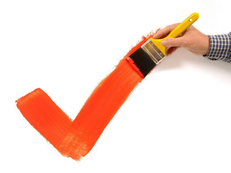Man painting a red tick or checkmark on a plain white wall.  Space for copy.